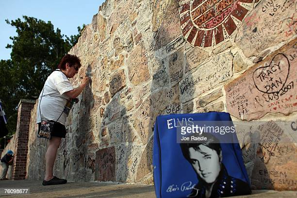 Kathy Scharff from Detroit Michigan signs the wall around the Graceland Mansion the home of Elvis Presley on August 14 2007 in Memphis Tennessee This...
