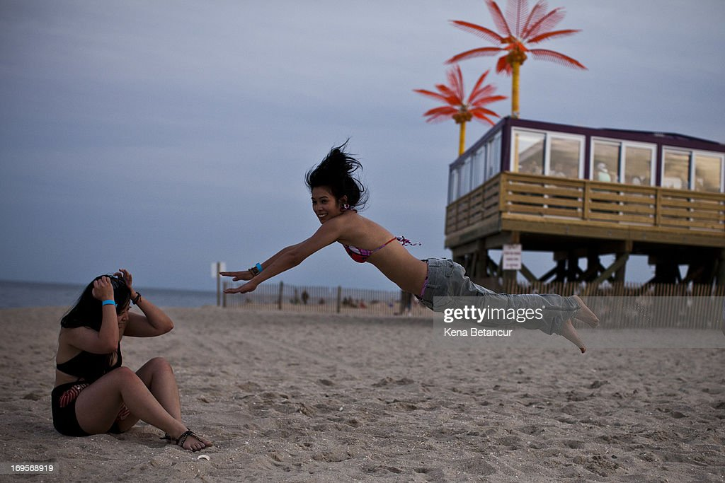 Kathyn S. jumps as she plays with friends at Point Pleasant Beach on the first weekend of New Jersey beaches re-opening to the public on May 27, 2013 in Point Pleasant, New Jersey. The region continues to recover and rebuild after Hurricane Sandy devastated parts of the coastline.