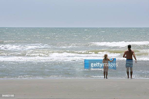 Katie Beachum left and her uncle Walt Richardson both of Fort Mill South Carolina test the water on Sunset Beach North Carolina US on Monday May 19...