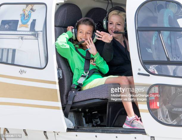 Katie Carlson left and her mother Christy wave to friends as they prepare to get a ride in the Orange County Sheriff's helicopter ///ADDITIONAL...
