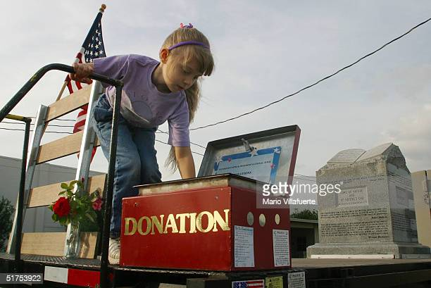 Katie Comer places a dollar bill in a donation box atop a flatbed truck displaying the granite Ten Commandments monument that was removed in 2003...