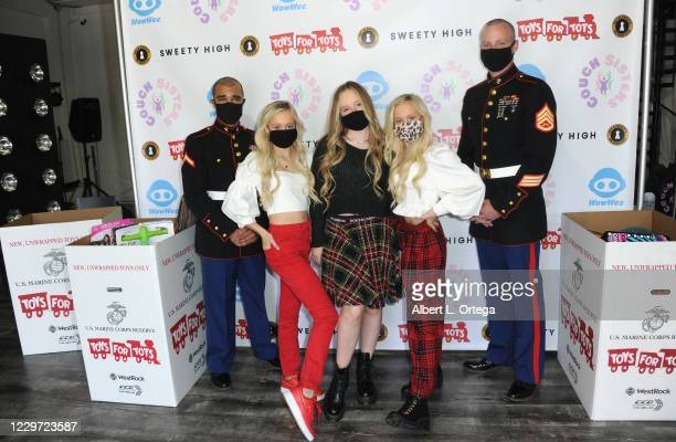 Katie Couch, Mackenzie Couch and Kameron Couch pose with United States Marines from Toys For Tots at the 2nd Annual Toys For Tots Toy Drive held at...