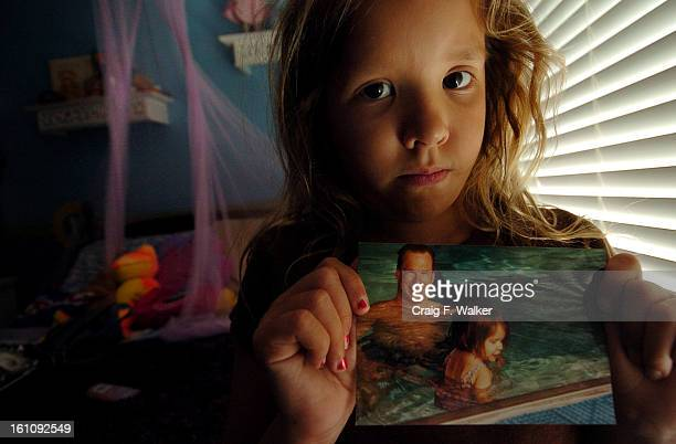 AUGUST 04 2006 WICHITA KS Katie displays a photograph of she and her late father at her home in Wichita KS where she lives with her brother JD their...