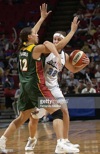 Katie Douglas of the Orlando Miracle gets tangled with Adia Barnes of the Seattle Storm in the game on July 25 2002 at TD Waterhouse Centre in...