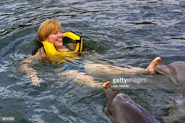 Katie Durant is pushed by two bottlenose dolphins during the structured swim May 4 2001 at the Dolphins Plus marine mammal research and education...