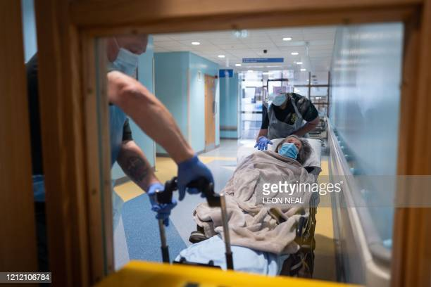 TOPSHOT Katie FfolloittPowell and Mike Carr of the Patient Transport Services of South Central Ambulance Services move an elderly nonCOVID19 patient...