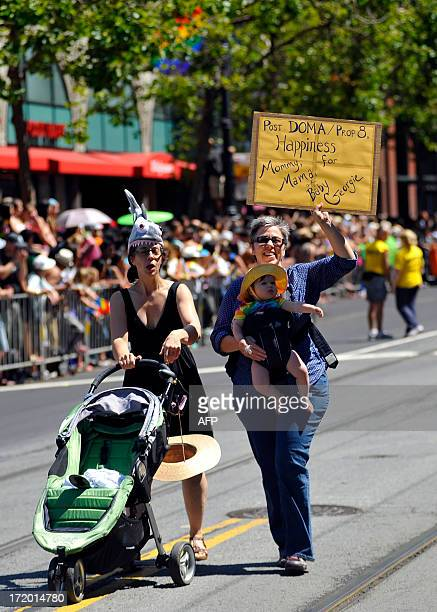 Katie Hern Teri Mae Rutledge and daughter Georgie Hern walk along the parade route of San Francisco's Gay Pride festival on June 2013 AFP PHOTO /...