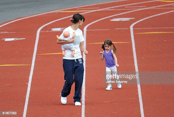 Katie Holmes and daughter Suri Cruise run track at a track field on October 12, 2009 in Boston, Massachusetts.