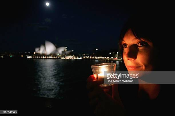 Katie Ibbotson from the Cruise Bar has a candle lit during Earth Hour March 31, in Sydney, Australia. The entire city of Sydney, including companies,...