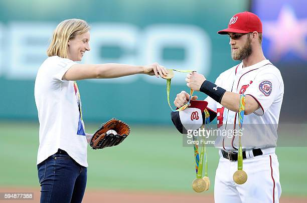 Katie Ledecky hands her Olympic medals to Bryce Harper before throwing out the opening pitch before the game between the Baltimore Orioles and the...