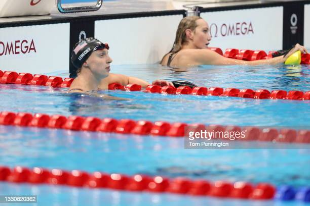 Katie Ledecky of Team United States and Madison Wilson of Team Australia look on during the Women's 200m Freestyle Semifinal 2 on day four of the...