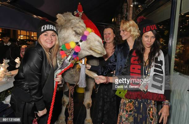 Katie Lyall Katie Grand Poppy Delevingne and Charlotte Stockdale pose with a camel at the Love x Chaos x Poppy Delevingne x Moet Christmas Party at...