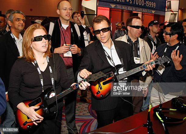 Katie Maloney and Adam Nettler play a Guitar Hero video game in 3D wearing NVIDIA GeForce 3D Vision glasses at the 2009 International Consumer...
