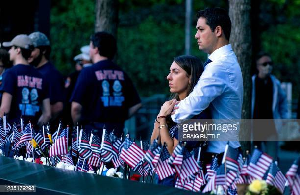 Katie Mascali is comforted by her fiance Andre Jabban as they stand near the name of her father Joseph Mascali, with FDNY Rescue 5, during ceremonies...