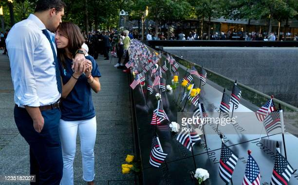 Katie Mascali is comforted by her fiance Andre Jabban as they stand near the name of her father Joseph Mascali during a ceremony at the National...