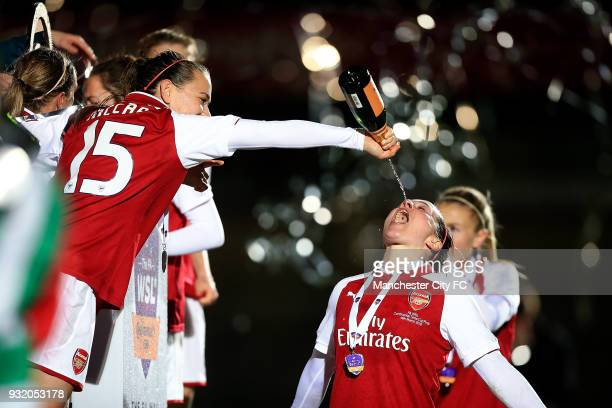 Katie McCabe of Arsenal pours champagne into Emma Mitchell's mouth as they celebrate winning the WSL Continental Cup Final between Arsenal Women v...