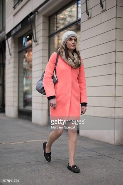 Katie McGraw is seen on Oak Street wearing grey cashmere/wool Club Monaco hat Badgley Mischka faux fur scarf bright salmon JCrew wool coat Goyard bag...