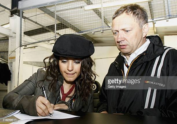 Katie Melua signs a document before she gets ready to be driven around the track in the two seater GP masters car during the GP Masters of Great...