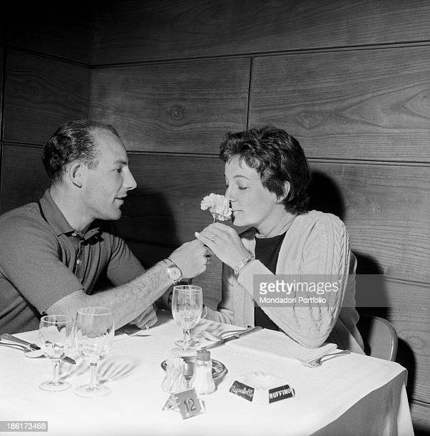 Katie Molson smelling a flower given to her by her partner and British racing driver Stirling Moss at the Mille Miglia Automobile Race Italy May 1957