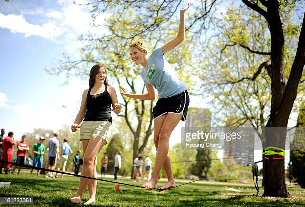 Katie Pellicore of East High School right is slacklining with the support of her friend Ally Beyer at City Park in Denver Colo on Tuesday April 24...