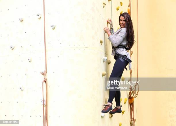 Katie Price climbs a wall as she attends the launch of Walkers Deep Ridged crisp at The Old Truman Brewery on August 29 2012 in London England