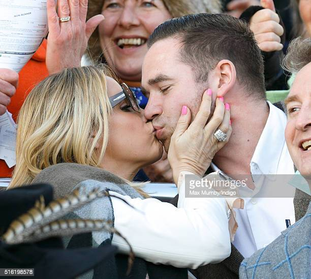 Katie Price kisses husband Kieran Hayler as they watch the racing on day 3 St Patrick's Day of the Cheltenham Festival on March 17 2016 in Cheltenham...