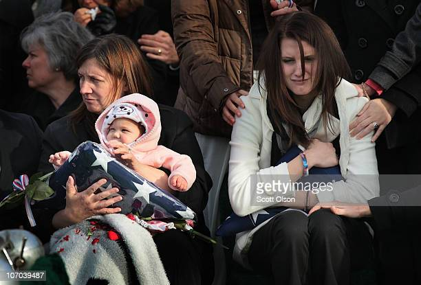 Katie Stack the wife of Marine Lance Cpl James Stack grips the flag from her husband's casket as she sits next to her oneyearold daughter Mikayla...