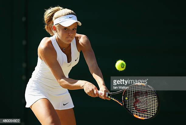 Katie Swan of Great Britain plays a backhand in her Girls Singles match against Viktoria Kuzmova of Slovakia during day ten of the Wimbledon Lawn...
