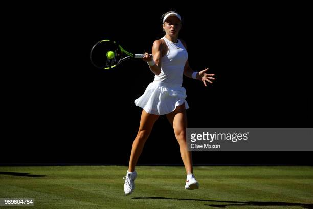 Katie Swan of Great Britain returns against IrinaCamelia Begu of Romania during their Ladies' Singles first round match on day one of the Wimbledon...