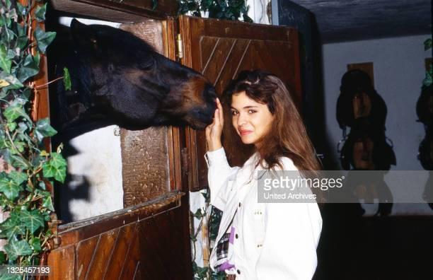 Katja Woywood, deutsche Schauspielerin, kümmert sich in ihrer Feizeit um Pferde, Deutschland um 1989.