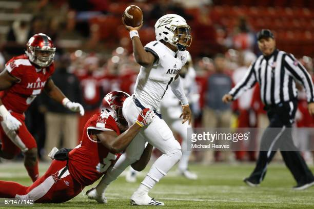 Kato Nelson of the Akron Zips throws a pass under pressure from Ikeem Allen of the Miami Ohio Redhawks during the second half at Yager Stadium on...