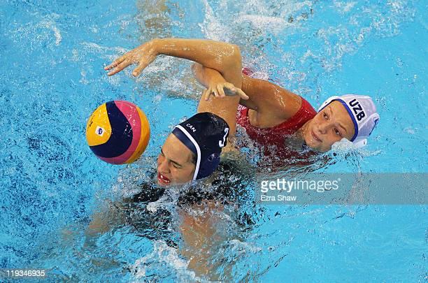 Katrina Monton of Canada attempts to control the ball against Anastasiya Osipenko of Uzbekistan during their Women's Water Polo first preliminary...
