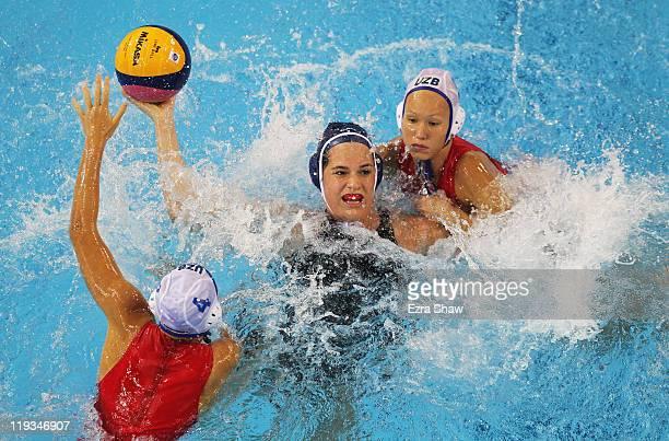 Katrina Monton of Canada looks to pass the ball against Eseniya Ivanova and Evgeniya Ivanova of Uzbekistan during their Women's Water Polo first...