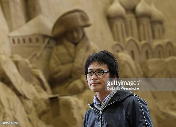 Katsuhiko Chaen Executive Director of Sand Museum looks on as Sand sculptors finish sculptures at the Sand Museum in the Tottori Dune on April 3 2014...