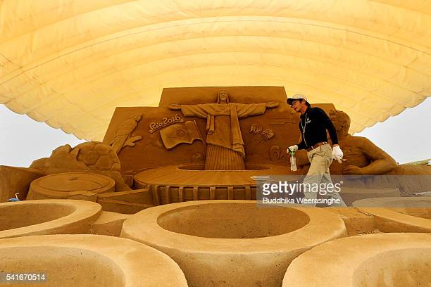 Katsuhiko Chaen sand sculptor and Executive Director of the Sand Museum takes break during the works on a Sand sculpture of the Olympic Rings below...