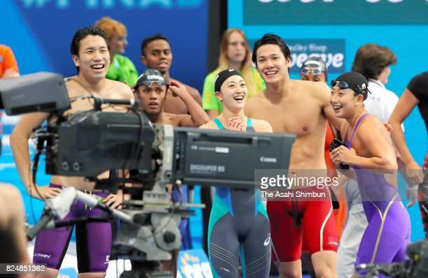 Katsuhiro Matsumoto Katsumi Nakamura Tomomi Aoki and Chihiro Igarashi of Japan pose for photographs after competing in the Mixed 4x100m Freestyle...