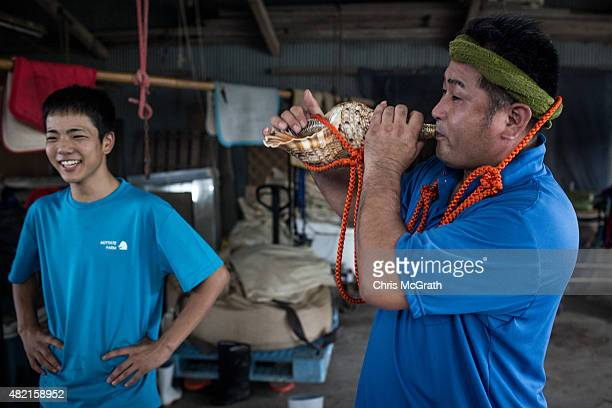 Katsuhiro Yamada, a Samurai for 18 years practices blowing a traditional conch shell horn at a horse stable during preparations for the Soma Nomaoi...
