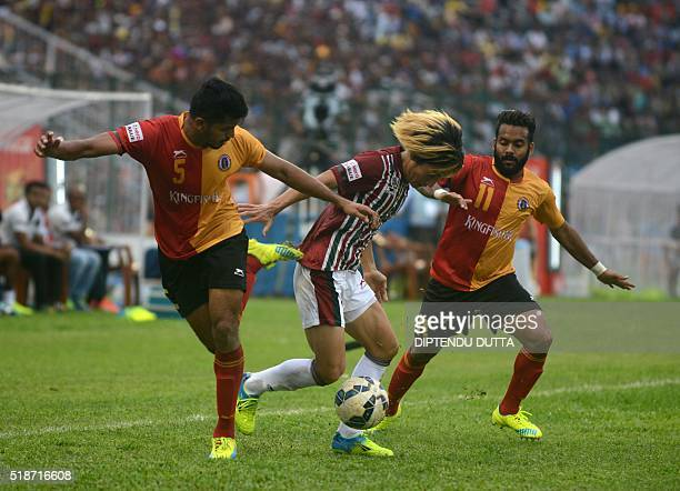 Katsumi Yusaof Mohun Bagan is tackled by East Bengal's Rahul Bheke and Cavin Peter Loboduring the ILeague football match at The Kanchenjungha Stadium...