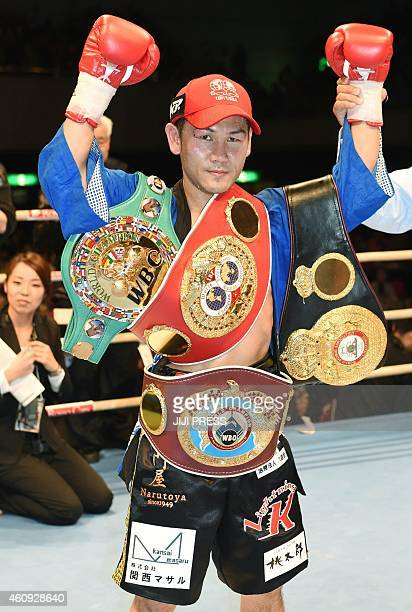 Katsunari Takayama of Japan raises his arms while showing his championship belts from the WBC IBF WBO and WBA after his title bout for the IBF/WBO...