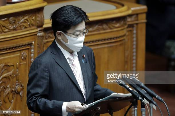 Katsunobu Kato, Japan's health minister, wearing a protective mask, speaks during a plenary session at the upper house of parliament in Tokyo, Japan,...