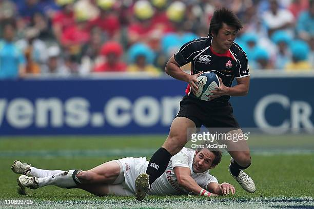 Katsuyuki Sakai of Japan gets out of the tackle of Ben Gollings of England during day two of the IRB Sevens at Hong Kong Stadium on March 26, 2011 in...