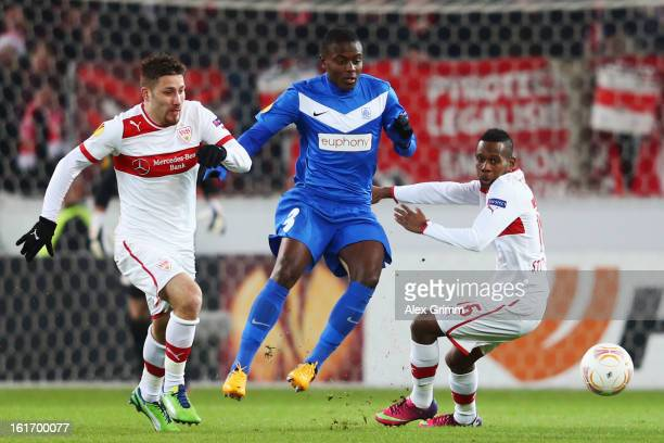 Katuku Tshimanga of Genk is challenged by Tunay Torun and Ibrahima Traore of Stuttgart during the UEFA Europa League Round of 32 first leg match...