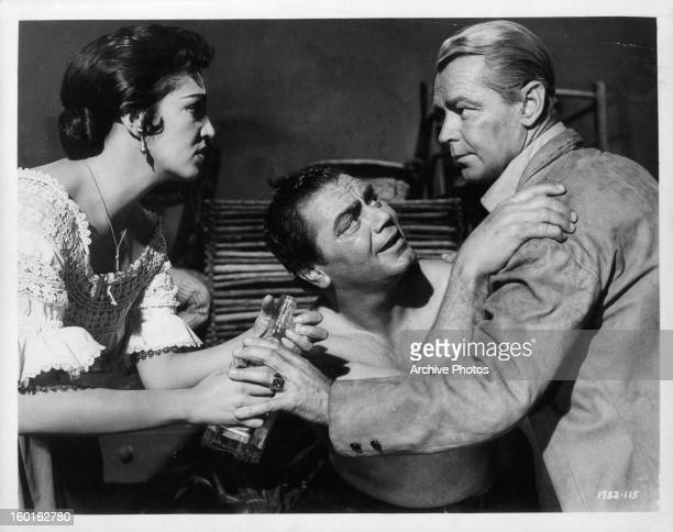 Katy Jurado holds a bottle as Ernest Borgnine grabs the shoulders of Alan Ladd in a scene from the film 'The Badlanders' 1958