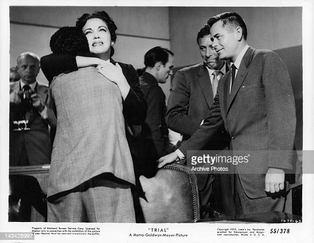 Katy Jurado hugging man as Glenn Ford watches in a scene from the film 'Trial' 1955