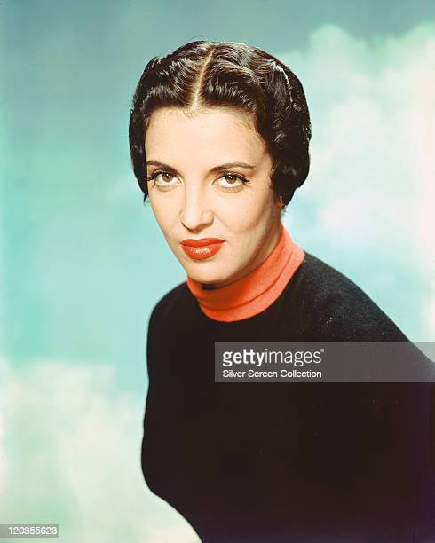 Katy Jurado Mexican actress wearing red polo neck top beneath a black jumper in a studio portrait against a background of blue sky and clouds circa...