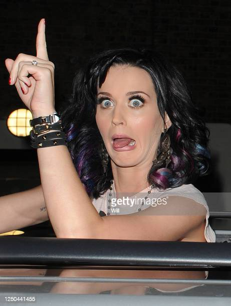 Katy Perry climbs out of the sunroof of her people carrier to sign autographs for fans outside the ITV studios on September 1 2010 in London England