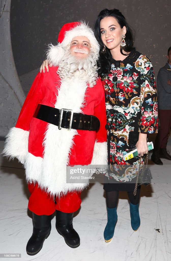 Katy Perry (R) poses for photos with Santa from 'A Christmas Story, The Musical' Broadway Performance at Lunt-Fontanne Theatre on December 12, 2012 in New York City.