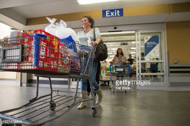 Katya Rivasplata pushes a large cart of supplies including Aloha Water in preparation for Hurricane Lane at Sam's Club on Wednesday August 22 2018 in...