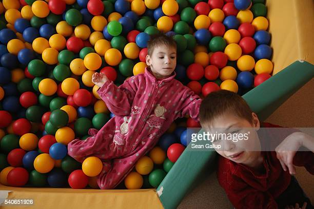Katya who is diagnosed with convulsive sydrome microcephaly and is the size of an infant lies in a pen of coloured balls next to a...