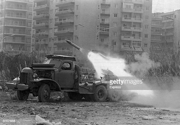 Katyusha rocket is fired from the back of an army truck into an apartment complex during the Lebanese Civil War, Lebanon, probably 1975. The war,...